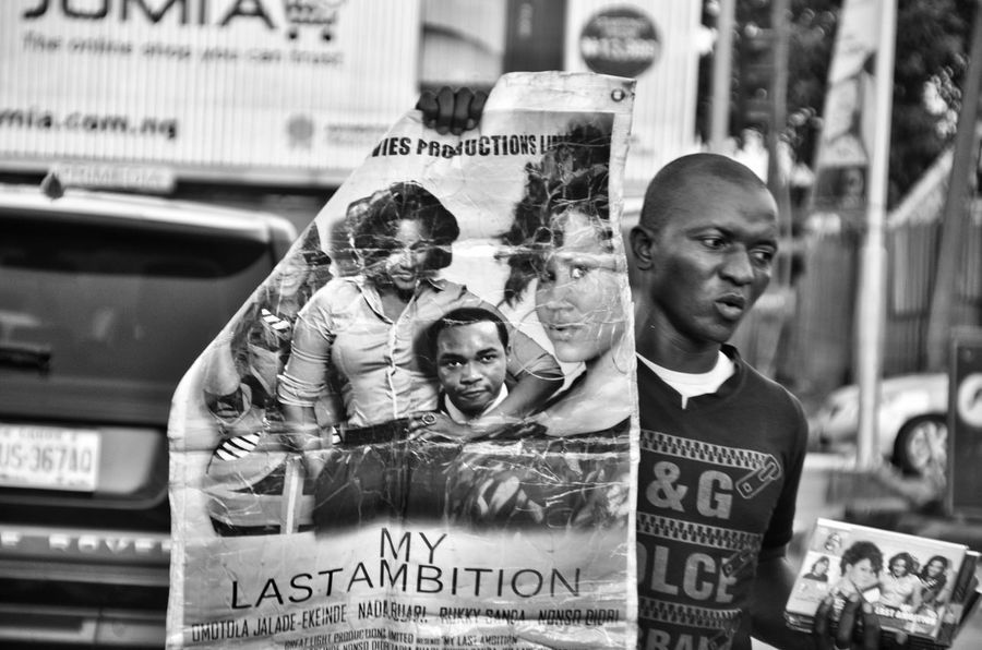 The Photojournalist - 2016 EyeEm Awards Street Style From Around The World Nigerian Street Trader Nigerian Movie Seller Streetphotography Streetphotography_bw Street Vendor The Street Photographer - 2016 EyeEm Awards Original Experiences