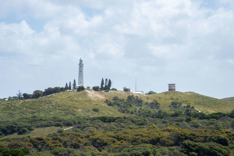 Wadjemup lighthouse in lush, green coastal landscape under a cloudy sky at Rottnest Island in Western Australia. Architecture Australia Building Exterior Cloudy Dunes Grassy Hill Hilltop Historical Building Island Landscape Lantern Room Lighthouse Outdoors Overcast Remote Rottnest Rottnest Island Scenics Tourist Attraction  Tower Travel Destinations Wadjemup Western Australia White