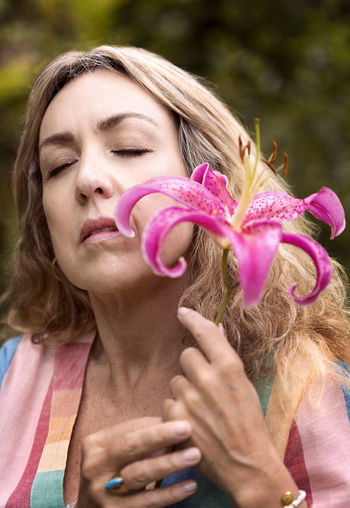 Close-up portrait of woman holding pink flower
