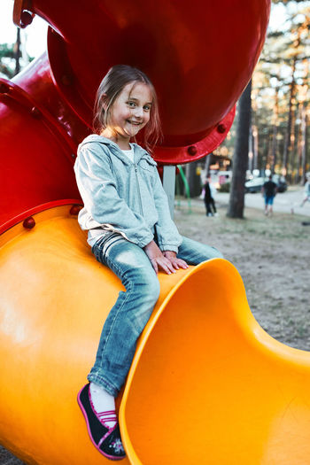 Little girl preschooler playing on a playground sitting on tube slide smiling and looking at camera