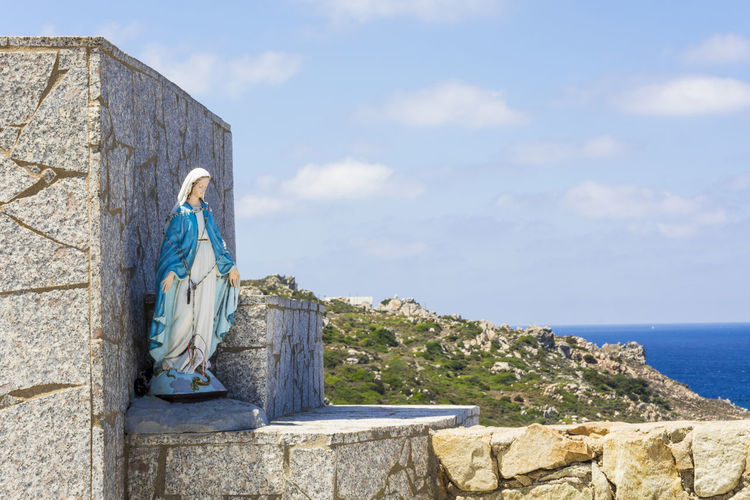 Virgin Mary Statue Outside Church By Sea Against Sky