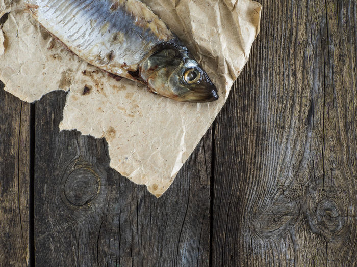 Close-up of herring on paper at table