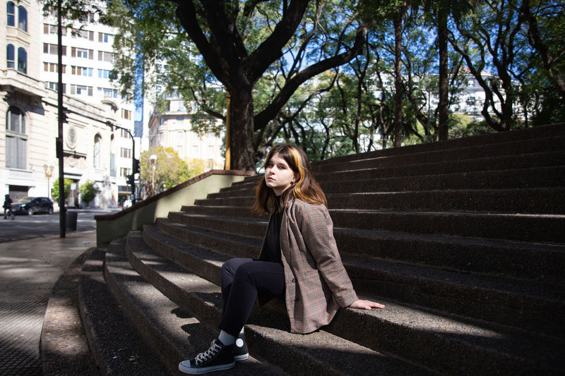 Woman sitting on staircase in city