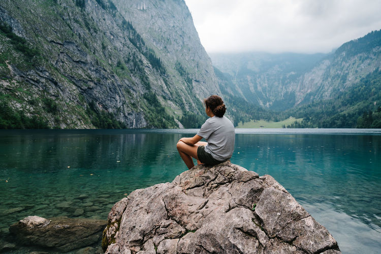 Girl looking at the lake Königssee Obersee Adult Adults Only Adventure Alps Beauty In Nature Cliff Day Full Length Lake Mountain Mountain Range Nature One Person One Woman Only Outdoors People Real People Rock - Object Scenics Sitting Sky Tranquility Tree Water Young Adult