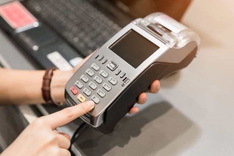 Concept of technology in buying without using cash. Close up of hand use credit card swiping machine to pay. Human Hand Hand Human Body Part Technology Number Business Adult One Person Close-up Communication Indoors  Finance Holding Wireless Technology High Angle View Women Table Businesswoman Connection Keypad Finger