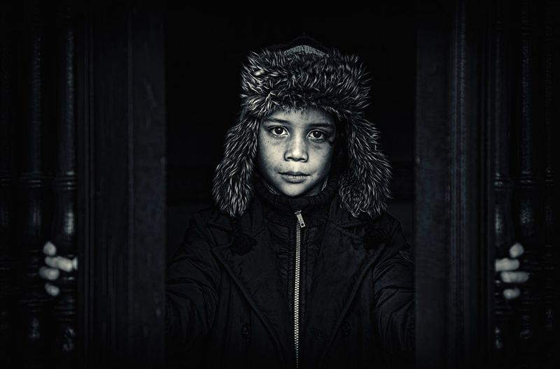 Portrait of boy wearing warm clothing while standing at doorway