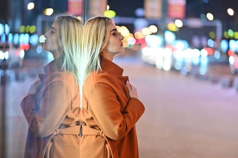 Side view of young woman standing on street at night