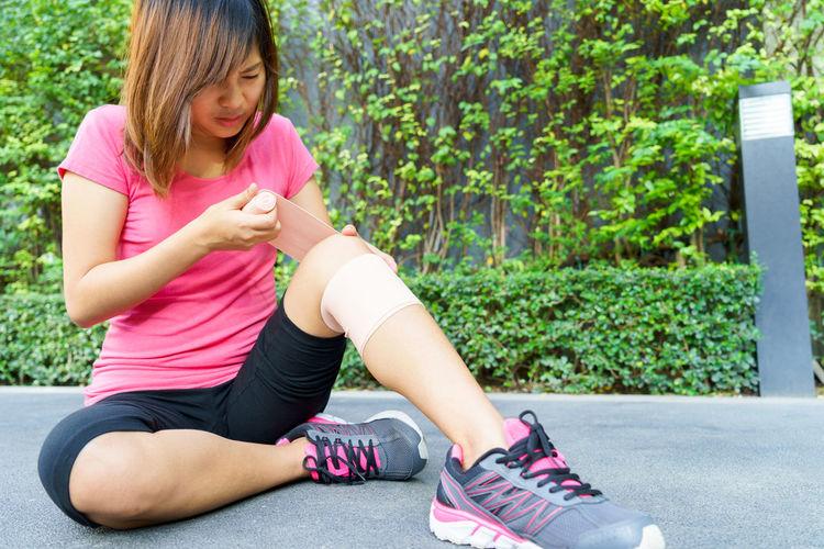 Full Length Of Young Woman Applying Adhesive Bandage On Leg