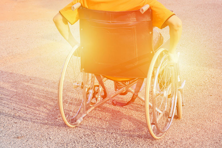 Rear View Of Man Sitting On Wheelchair During Sunny Day