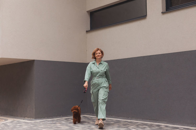 Full length of woman walking with dog against wall