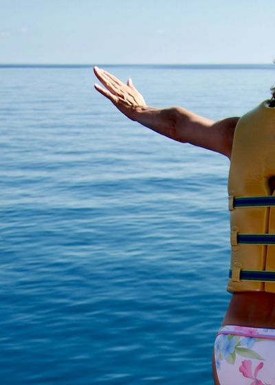 Close-up of woman with life jacket against sea