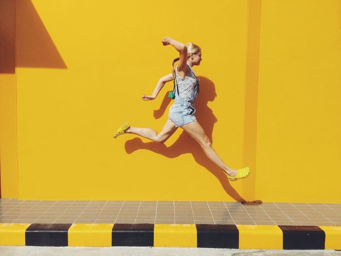 Side view of mid adult woman jumping on footpath against yellow wall