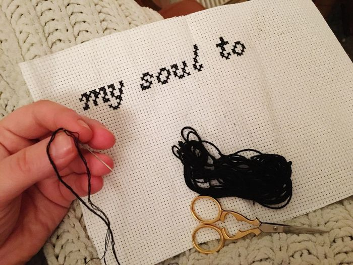 Cropped hand of woman writing with wool on fabric