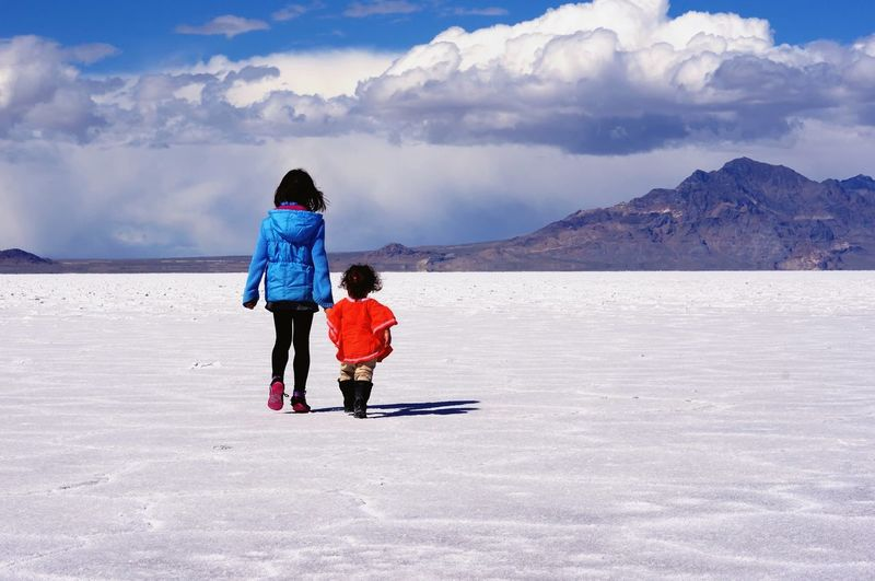 Two young girls walking across Great Salt Flats Girls Salt Lake City Great Salt Flats Utah Childhood Sky Cloud - Sky Two People Togetherness Rear View Real People Leisure Activity Elementary Age Nature Child Outdoors Landscape People Beauty In Nature Scenics Bonding Day