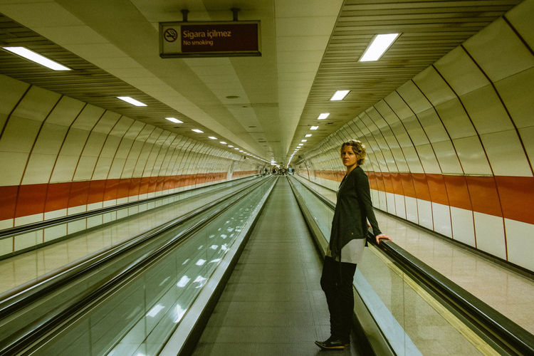 Side View Of Woman Standing By Railing On Moving Walkway