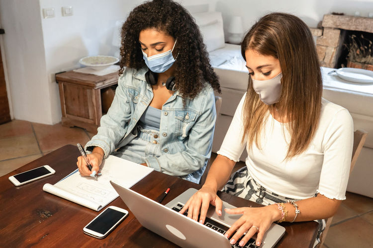 High angel view of businesswoman wearing mask working at home