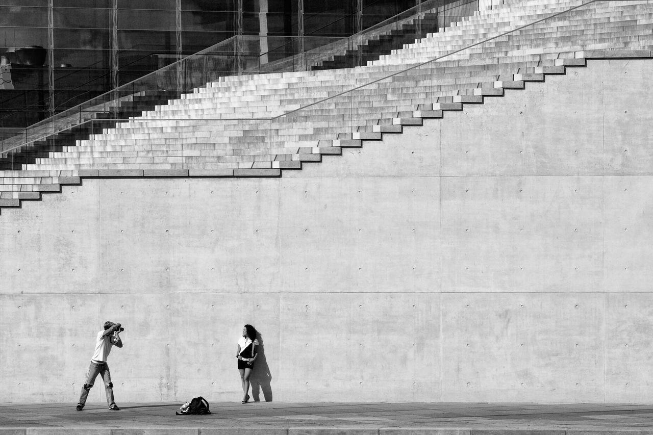 MAN STANDING ON ESCALATOR