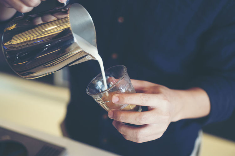 Midsection of man pouring milk in glass at cafe