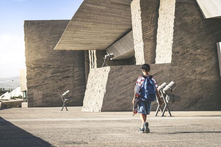 Full length rear view of boy walking on footpath