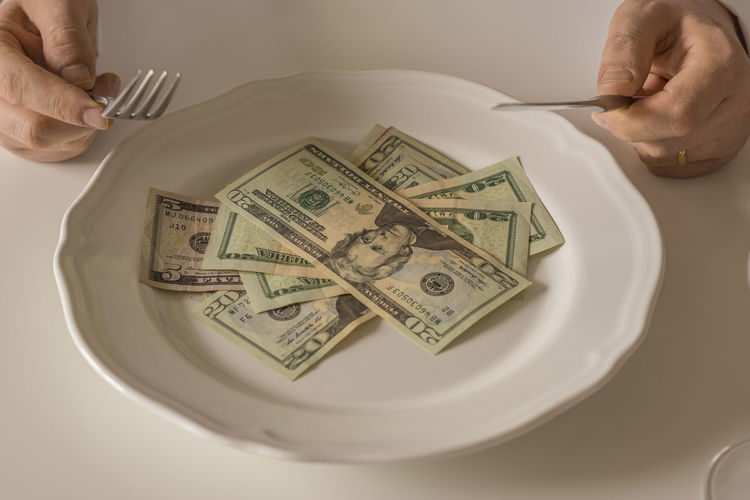Cropped hands with paper currency in plate on table