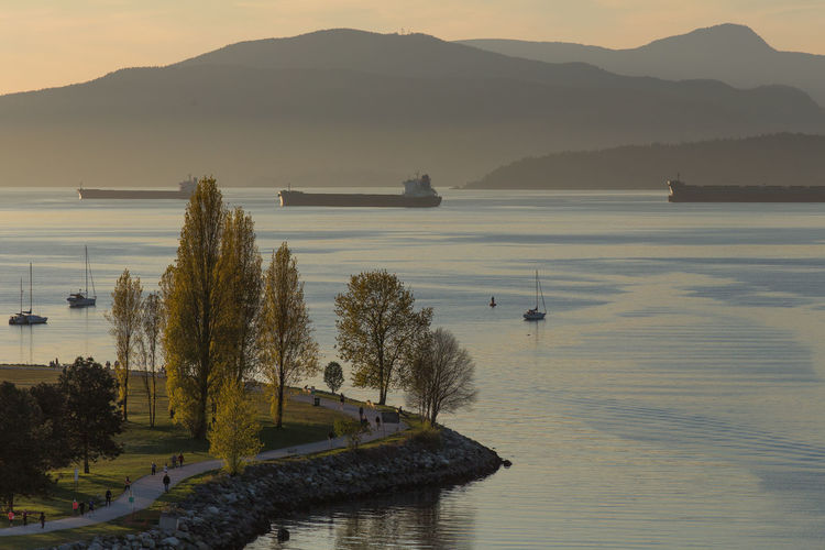 Scenic view of english bay by mountains during sunset
