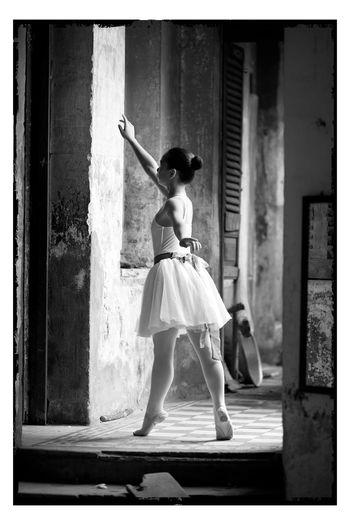 Ballet dancer tiptoeing in abandoned building corridor
