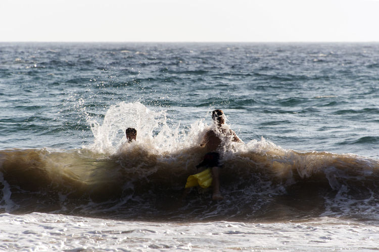 People playing, swimming in the waves in the island of Patmos, Greece in summer time Beach Beauty In Nature Breaking Day Horizon Horizon Over Water Land Motion Nature No People Outdoors Power In Nature Scenics - Nature Sea Sky Splashing Sport Water Waterfront Wave