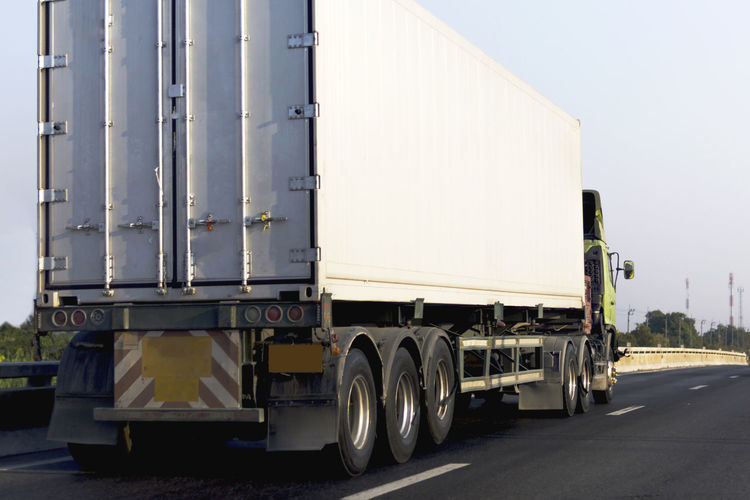 truck on road Transportation Truck Mode Of Transportation Land Vehicle Semi-truck Freight Transportation Trucking Commercial Land Vehicle Road Industry Business Motor Vehicle Motion Large Day Outdoors Nature Vehicle Trailer No People Container Wheel Container Transport White