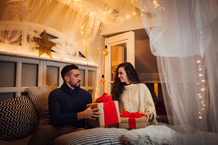 Young Couple Opening Christmas Gifts While Sitting On Bed At Home
