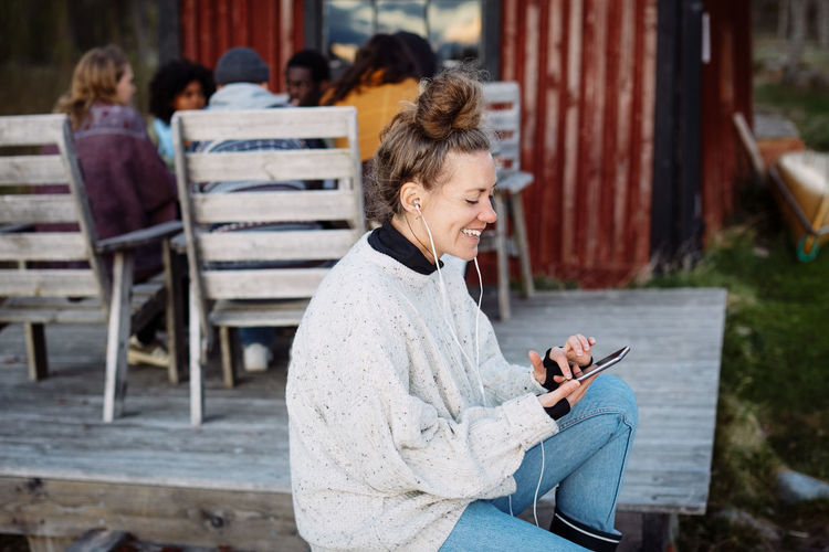 Side view of woman using phone while sitting on seat