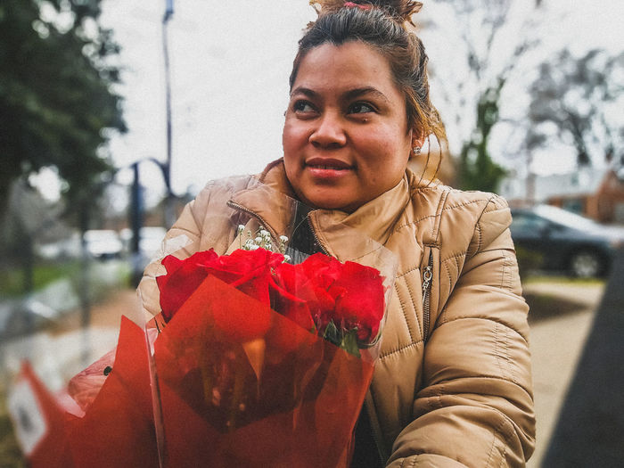 Close-Up Of Woman With Bouquet In City