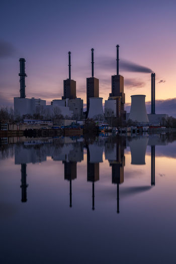 Reflection of factory in lake against sky during sunset