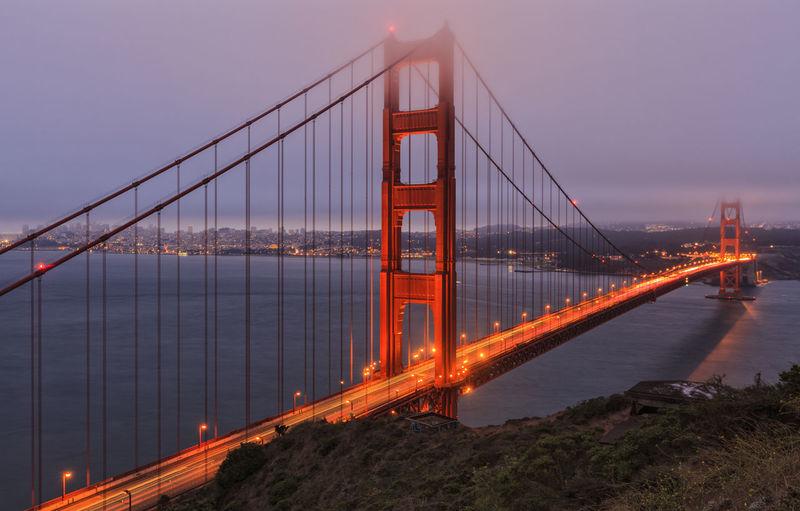 Illuminated golden gate bridge over sea against cloudy sky during sunset