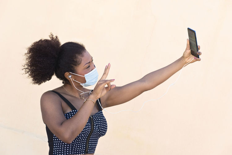 Midsection of person holding mobile phone while standing against wall