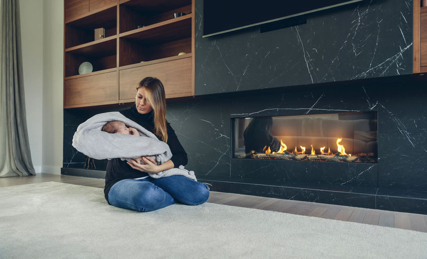Young mother hugging her newborn baby daughter in front of the fireplace Baby Beautiful Calm Home Horizontal Hugging Lying Mother Tranquility Blanket Child Comfortable Cute Female Fireplace Girl Heat Lovely Newborn Real People Relaxed Resting Sweet Tenderness Two People