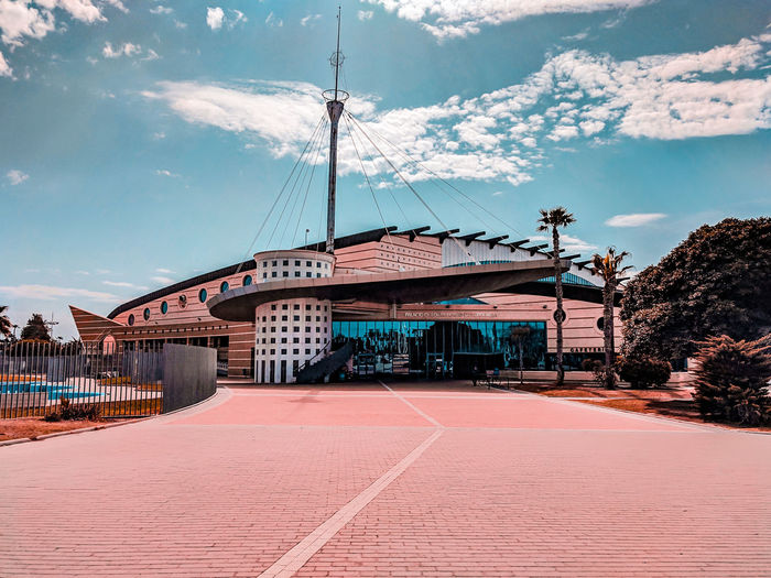 Torrevieja sport center, sunlit Coral Colored Sport Center Architecture Modern Architecture Sunlight Sunlit Rays Of Light Rays Of Sunshine Fluffy Clouds Pavement Sport Sports SPAIN Politics And Government Arts Culture And Entertainment Sky Architecture Cloud - Sky Pastel Colored Pale Pink