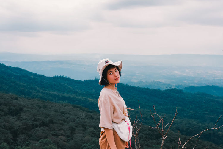 Young woman standing against mountains against sky