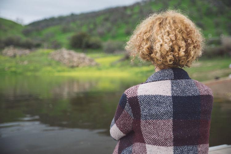 Rear view of woman by lake
