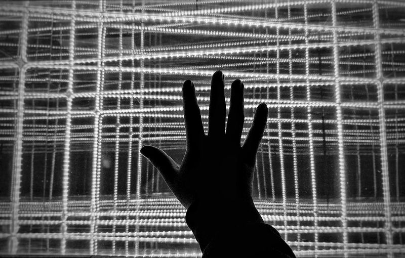 Close-up of silhouette hand touching illuminated light