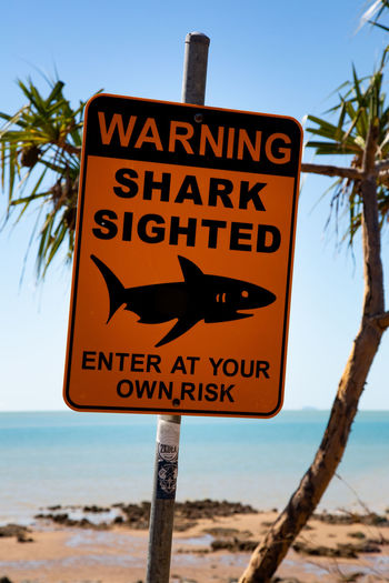 Close-up of warning sign on beach against sky