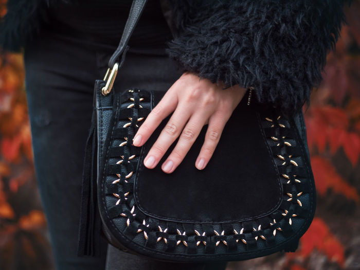 Close-up midsection of woman holding bag