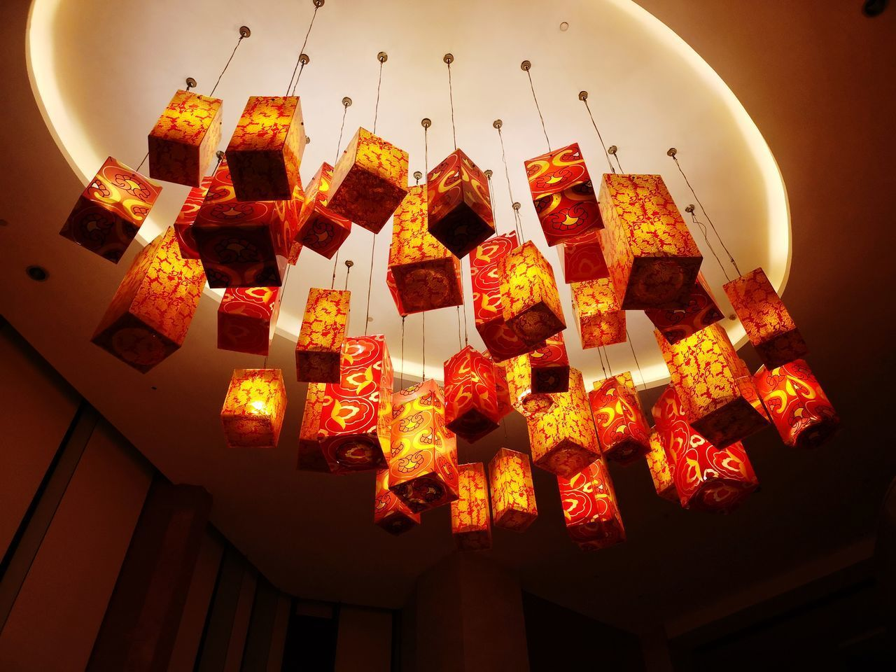 LOW ANGLE VIEW OF ILLUMINATED LANTERNS HANGING IN TRADITIONAL