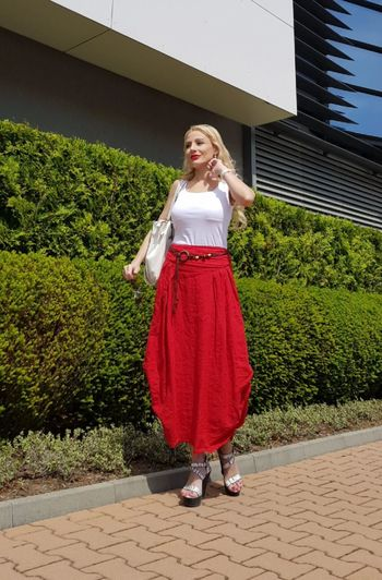Full length of fashionable woman standing on footpath by plants