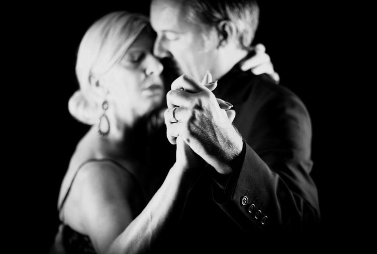 Close-up of couple dancing while holding hands against black background