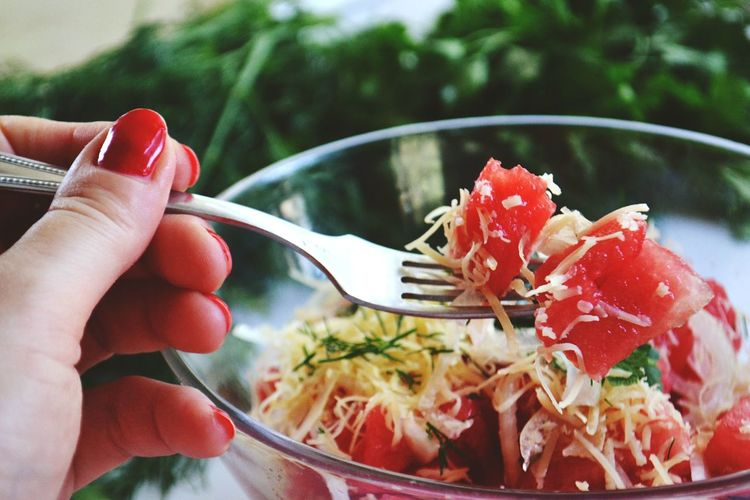 Cropped image of woman holding fork and bowl of food
