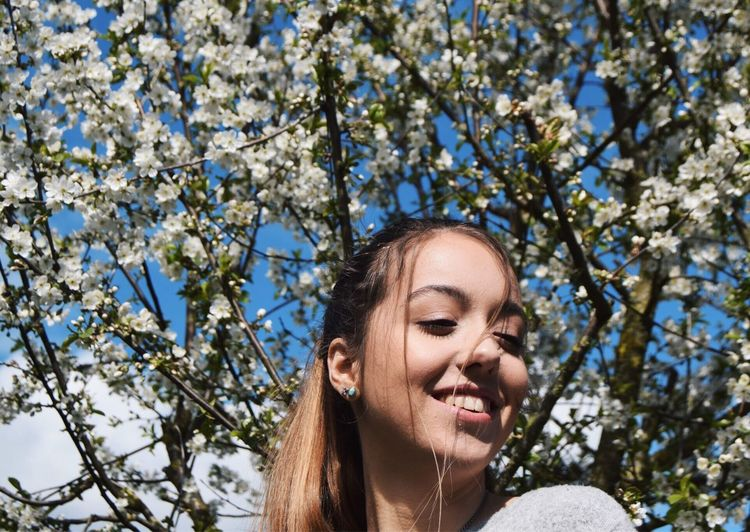 Young Woman Smiling Against Flowering Tree