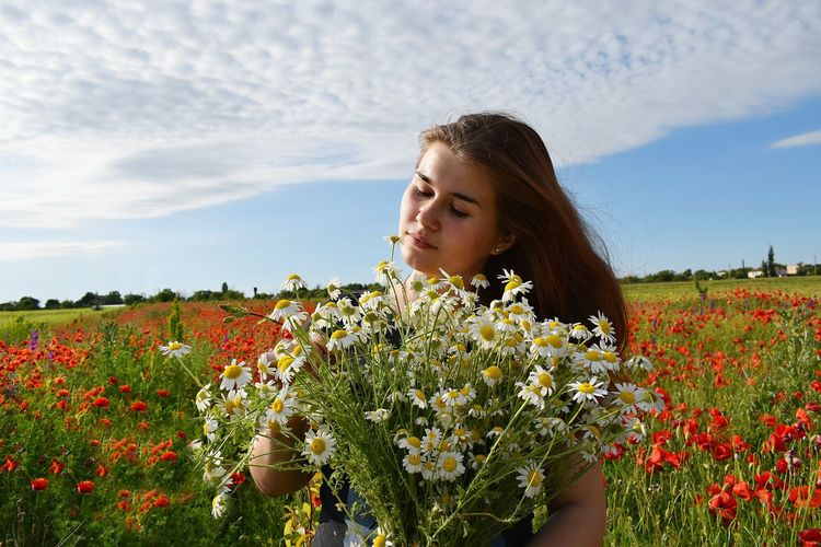 Beautiful young woman holding flowers in poppy field against sky