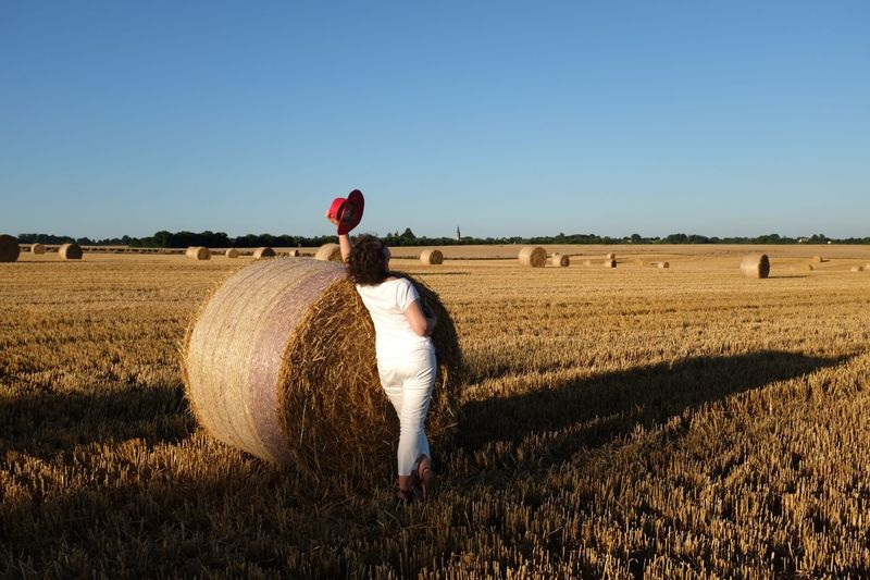 Rear View Of Woman Leaning On Hay Bale At Farm Against Clear Sky