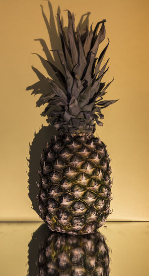Close-Up Of Pineapple On Table Against Beige Background