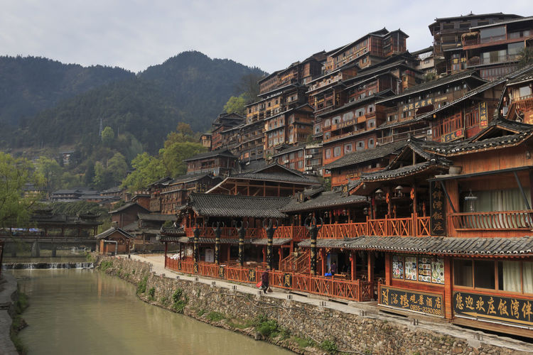 Traditional buildings by river against mountain
